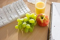 Bunch of grapes, apple and orange juice on office desk, close-up, elevated view still life