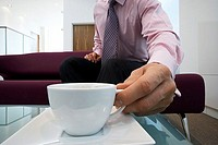 Businessman sitting on sofa in office lobby, placing cup on coffee table, close-up, surface level