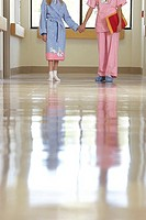 Nurse and patient walking along hospital corridor, front view, surface level