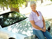 Senior woman sitting on bonnet of convertible car, smiling, portrait tilt