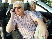Senior couple sitting in convertible car, man in sunglasses using mobile phone, smiling, side view
