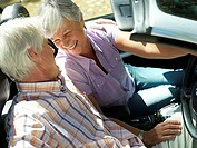 Senior couple sitting in convertible, face to face, smiling, side view tilt