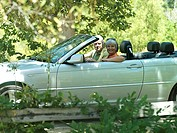 Senior couple driving in convertible car along country road, side view, smiling, portrait