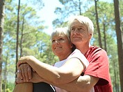 Senior couple in sportswear sitting in wood, man embracing woman, smiling, low angle view