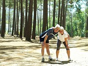 Senior couple in sportswear taking break from jogging, leaning on knees, smiling, portrait