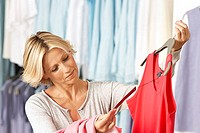 Mature woman shopping in clothes shop, holding red vest top on coathanger, checking price tag, smiling