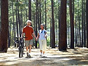 Senior couple in cycling helmets walking through wood with bicycles, holding hands, front view