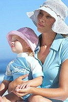 Mother and daughter 2-4 in sun hats sitting on beach, girl in woman's lap, close-up