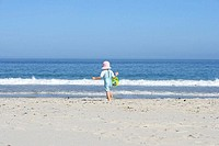 Girl 3-5 walking on sandy beach with bucket and spade, rear view, sea in background