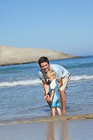 Father and daughter 2-4 standing ankle deep in water on beach, side view, smiling, portrait tilt