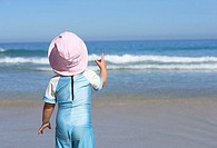 Girl 2-4 in pink sun hat standing on sandy beach, looking at horizon over sea, rear view