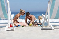 Two generation family building sandcastles on sandy beach, deckchairs in foreground