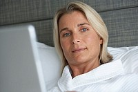 Businesswoman in bathrobe lying in hotel bed, using laptop, close-up, portrait