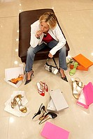 Mature blonde woman trying on different pairs of high heels in shoe shop, hand on chin, thinking, elevated view