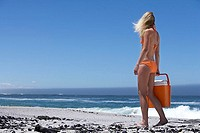 Young woman in orange bikini carrying cooler on beach, looking at horizon over sea, rear view