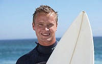 Young man in wetsuit standing on beach with surfboard, smiling, front view, close-up, portrait