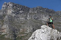 Male mountain biker sitting on bicycle at edge of rock, looking at view, side view, low angle view