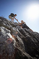 Rock climbing couple ascending rock, man offering woman helping hand, smiling, low angle view