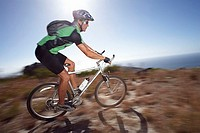 Male mountain biker cycling across extreme terrain in bright sunlight, sea in background, side view