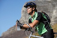 Male mountain biker sitting on bicycle, looking at view, holding water bottle, profile