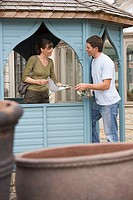 Couple shopping for gazebo in garden centre, woman holding brochure, talking, side view