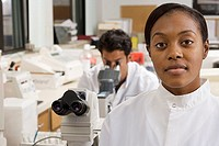 Two medical lab technicians working with microscope in hospital lab, focus on woman in foreground