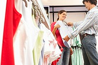 Couple shopping in clothes shop, man holding pale blue top up against girlfriend, smiling, side view (thumbnail)
