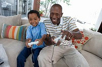 Father and son 7-9 playing video games console on sofa at home, smiling, front view
