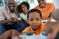 Family playing video games console on sofa at home, smiling, front view differential focus
