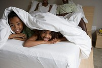 Two generation family lying beneath sheets on double bed, focus on children 6-9 in foreground