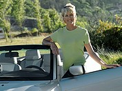 Mature woman standing beside convertible car, smiling, portrait