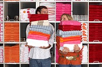 Couple shopping in department store, holding two large piles of towels beside shelf, faces obscured