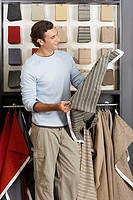 Man looking at grey fabric swatch in shop, smiling, side view