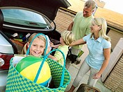 Family loading car boot with luggage, girl 6-8 holding bag, smiling tilt