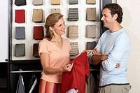 Couple standing beside fabric swatch display in shop, woman holdind red textile sample, smiling