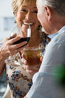 Senior couple sitting in restaurant, woman drinking red wine, smiling