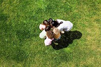 Teacher standing in huddle with children 3-5 on grass, overhead view