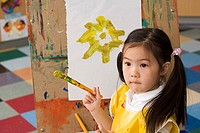 Girl 3-5 painting picture of yellow flower on easel in classroom, holding paintbrush
