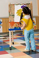 Girl 3-5 painting picture on easel in classroom, rear view