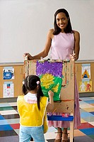 Girl 3-5 painting picture on easel in classroom, teacher looking on, smiling, portrait