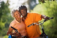 Active senior couple standing with bicycles in park, cheek to cheek, smiling, portrait tilt