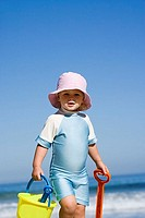 Girl 2-3 in sun hat standing on beach with bucket and spade, portrait