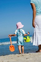 Girl 2-3 in sun hat walking on beach with mother, carrying bucket and spade, rear view