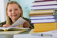 Girl 9-11 reading textbook at desk in classroom, smiling, portrait differential focus