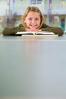 Girl 9-11 reading textbook at desk in classroom, smiling, front view, portrait, surface level