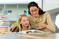 Girl 9-11 reading book at desk in classroom, female teacher assisting, smiling, surface level
