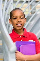 Boy 10-12 in red polo shirt holding school books and folders, smiling, portrait