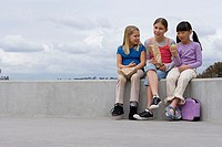 Three girls 9-11 sitting on wall outside school, eating packed lunch, smiling