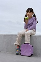 Girl 9-11 with purple schoolbag sitting on wall, eating apple at lunch, smiling, portrait