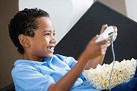 Boy 4-6 playing with games console at home, full bowl of popcorn in lap, smiling, close-up, side view
